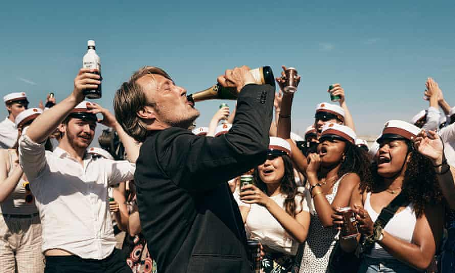 Mads Mikkelsen drinking from a bottle in front of a crowd of people.